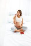 Gravid kvinna som hemma äter jordgubben sund begreppsmat royaltyfri fotografi