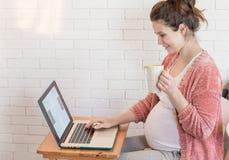 Gravid kvinna som hemma arbetar på bärbara datorn royaltyfri foto