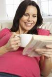 Gravid kvinna som hemma dricker den varma drinken och läseboken Fotografering för Bildbyråer