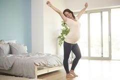 Gravid kvinna som hemma kopplar av royaltyfri bild