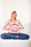 Gravid kvinna som hemma kopplar av på soffan royaltyfria foton