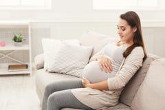 Gravid kvinna som hemma smeker hennes buk arkivbild