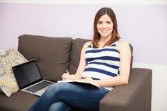 Gravid kvinna som hemma tar anmärkningar Arkivbild