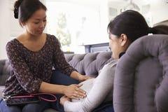 Gravid kvinna som hemma undersöks av barnmorskan arkivfoton