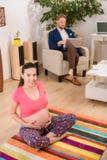 Gravid kvinna som hemma utbildar Arkivfoto