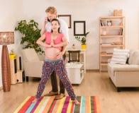 Gravid kvinna som hemma utbildar Arkivbild
