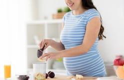 Gravid kvinna som hugger av hemmastatt k?k f?r frukter arkivbild