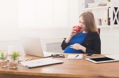 Gravid kvinna som i regeringsställning äter kopieringsutrymme för äpple Arkivfoto
