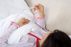 Gravid kvinna som kontrollerar hennes kroppstemperatur Royaltyfria Bilder