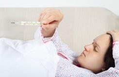 Gravid kvinna som kontrollerar hennes kroppstemperatur Arkivfoto