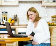 Gravid kvinna som kopplar av med hennes bärbar dator Royaltyfri Foto