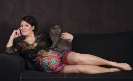 gravid kvinna som kopplar av på en soffa med en katt Fotografering för Bildbyråer