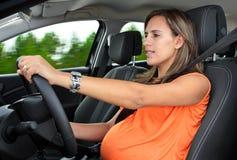 Gravid kvinna som kör en bil Arkivbild