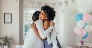 Gravid kvinna som kramar en vän på baby shower Arkivbilder