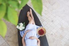 Gravid kvinna som lägger på en soffa royaltyfria foton