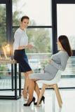 Gravid kvinna som ler medan en nyfiken kollega som pekar till hennes buk arkivfoto
