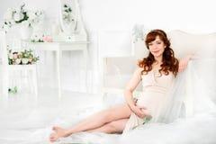 Gravid kvinna som ligger i den härliga beigea klänningen som griper hans mage med hans händer Royaltyfria Bilder