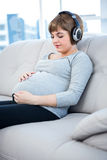 Gravid kvinna som lyssnar till musik, medan sitta i vardagsrum Arkivfoto