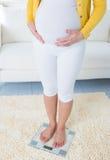 Gravid kvinna som mäter henne, väger till och med vägning av fjäll Arkivbild