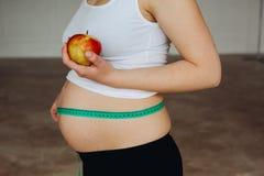 Gravid kvinna som mäter hennes stora gravida buk med att mäta familjer Mamman förväntar en behandla som ett barn Begreppet av royaltyfri foto