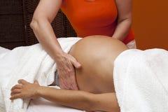 Gravid kvinna som mottar avslappnande massage arkivfoto