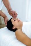 Gravid kvinna som mottar en head massage från massör royaltyfri foto