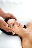 Gravid kvinna som mottar en head massage från massör royaltyfri bild