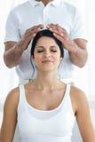 Gravid kvinna som mottar en head massage från massör royaltyfria bilder