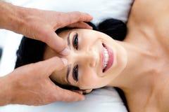 Gravid kvinna som mottar en head massage från massör arkivfoton
