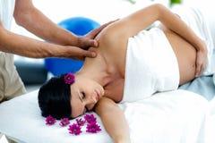 Gravid kvinna som mottar en tillbaka massage från massör royaltyfria bilder