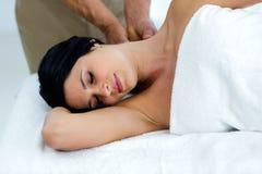 Gravid kvinna som mottar en tillbaka massage från massör Arkivbilder