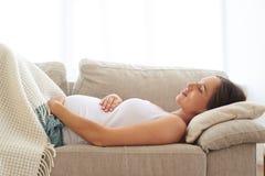 Gravid kvinna som omfamnar buken, medan sova på baksida arkivfoton