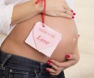 Gravid kvinna som omfamnar hennes buk Fotografering för Bildbyråer