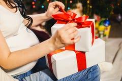 Gravid kvinna som packar upp julasken Royaltyfria Foton