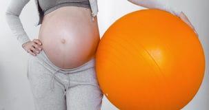 Gravid kvinna som rymmer en konditionboll arkivfilmer