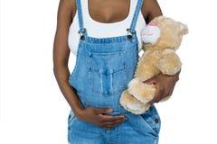 Gravid kvinna som rymmer en nallebjörn Arkivbild