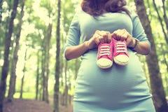 Gravid kvinna som rymmer ett par av rosa gymnastikskolitet barnskor Fotografering för Bildbyråer