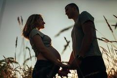Gravid kvinna som rymmer händer med hennes make mot bakgrund av himmel och spikelets arkivfoto