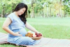 Gravid kvinna som rymmer hennes buk och sunda frukt Royaltyfri Fotografi