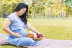 Gravid kvinna som rymmer hennes buk och sunda frukt som goda för hälsa Arkivbild