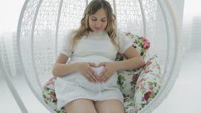 Gravid kvinna som rymmer hennes händer i en hjärtaform på hennes gravida buk lager videofilmer