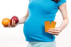 Gravid kvinna som rymmer nya mogna frukter och medicinska preventivpillerar eller tillägg, val mellan sund mat och preventivpille Arkivfoton