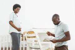 Gravid kvinna som ser mannen som läser en lista, medan fixa en behandla som ett barnstol arkivfoton