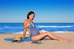 Gravid kvinna som sitter på den blåa strandsanden Royaltyfria Bilder
