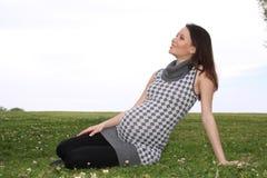 Gravid kvinna som sitter på en lawn arkivfoton