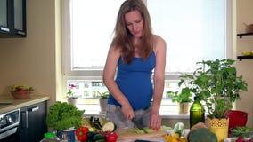 Gravid kvinna som skivar selleri med kniven för sallad på skärbräda lager videofilmer
