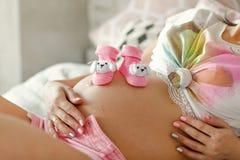 Gravid kvinna som tillbaka ligger p? henne, byten i hennes h?nder, h?rlig kropp av en gravid kvinna arkivfoton