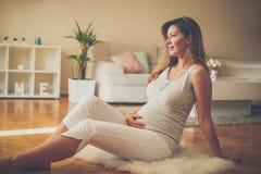 Gravid kvinna som trycker på hennes buk och sitter på golv fotografering för bildbyråer