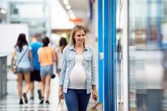 Gravid kvinna som trycker på i köpcentret som går Arkivfoton