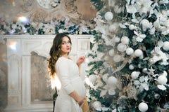 Gravid kvinna som upp klär en julgran nytt år Arkivfoton